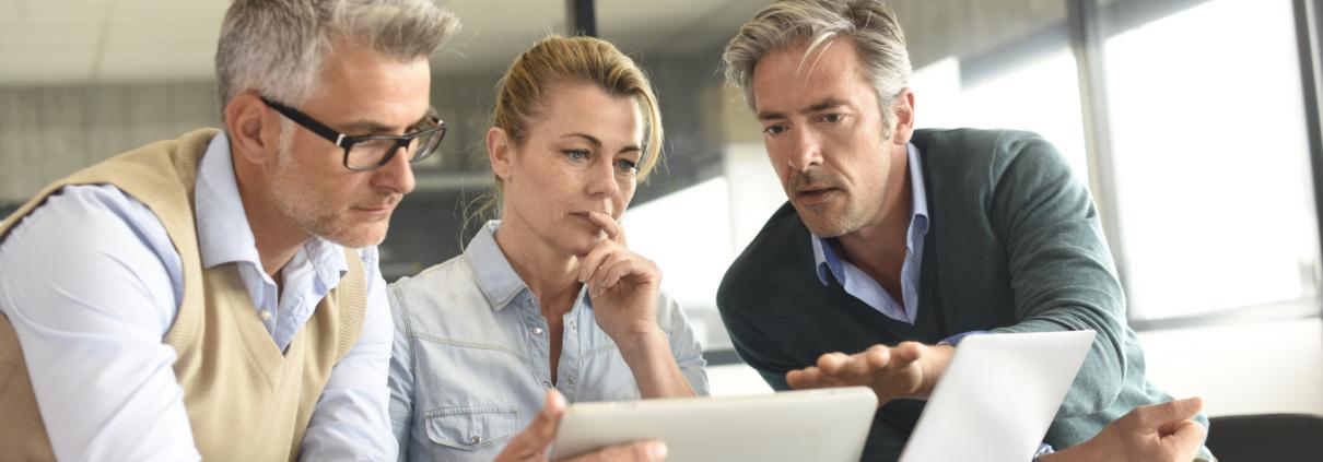 Ein Coach im Unternehmen und zwei Führungskräfte arbeiten an beruflicher Entwicklung.