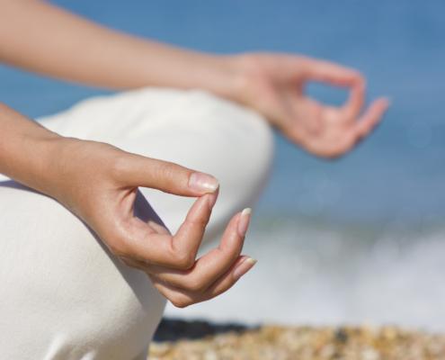 Eine Frau übt Yoga nahe dem Meer. Wunderschöne Meditationsatmosphere